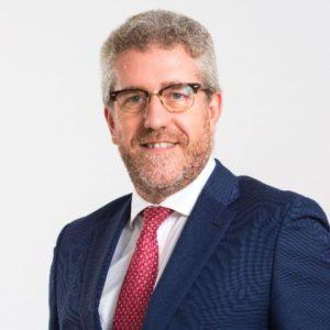 Un hombre vestido con traje y corbata sonriente