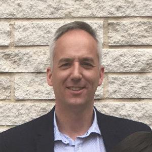 Un hombre con camisa y chaqueta, profesor del Máster en Industria 4.0, con una pared de fondo