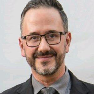 Profesor del máster en dirección de operaciones con gafas y corbata sonriendo