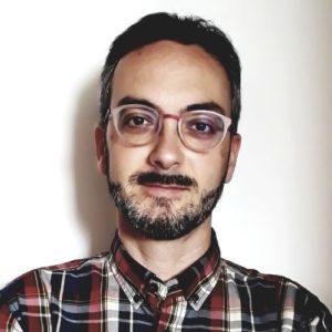 Un chico con gafas y barba, profesor del Máster en Industria 4.0, con una camisa de cuadros