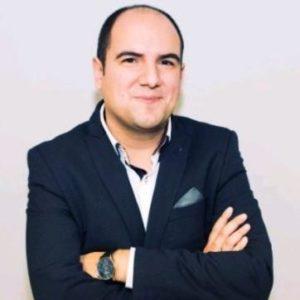 Un hombre con chaqueta, profesor del Máster en Industria 4.0, sonriendo y con los brazos cruzados