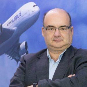 Un hombre, profesor del Máster en Industria 4.0, con una imagen de un avión de fondo