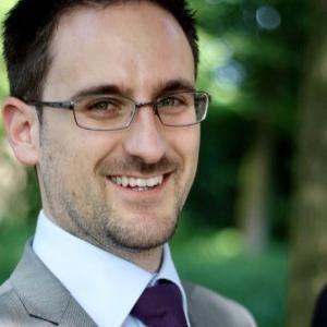 Un profesor del Máster en Dirección de Operaciones con gafas y corbata sonriendo