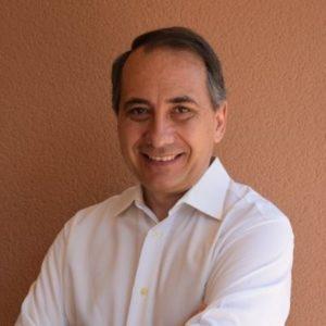 Un hombre, profesor del Máster en Dirección de Operaciones, sonriente y con una camisa blanca