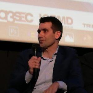 Un hombre, profesor del Máster en Industria 4.0, sostiene un micrófono para hablar