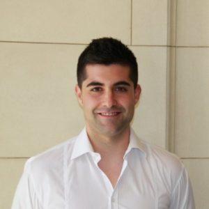 Un chico, profesor del Máster en Industria 4.0, con camisa blanca sonriendo