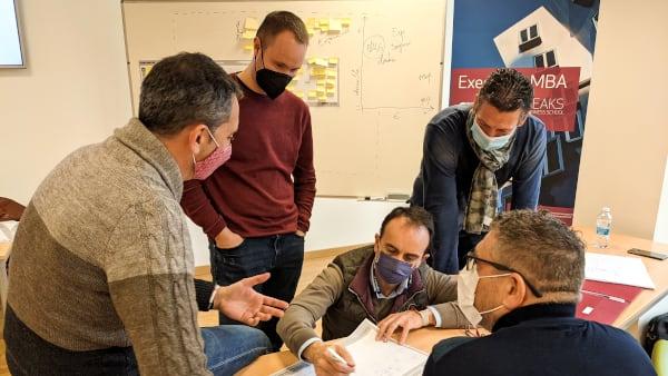 Un grupo de alumnos del Executive MBA de PEAKS Business debaten sobre una actividad al rededor de la mesa